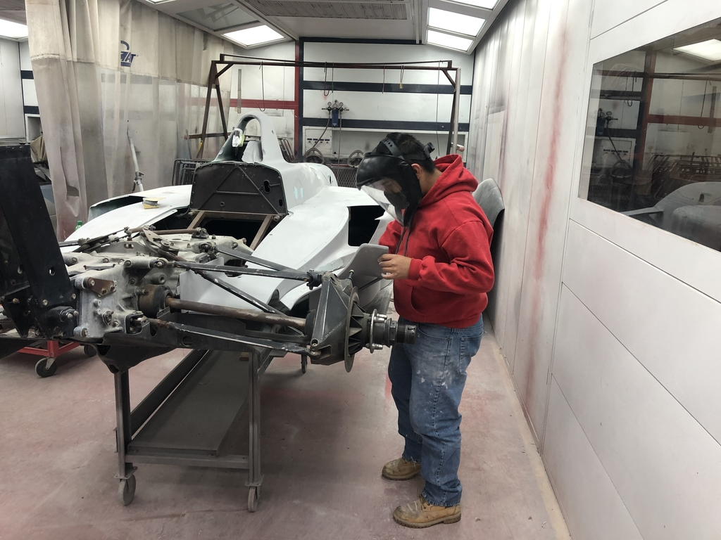 Student prepping our Indy Car for paint.