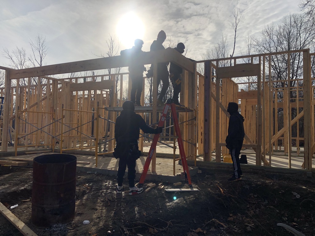 Students working on framing the construction trades home.