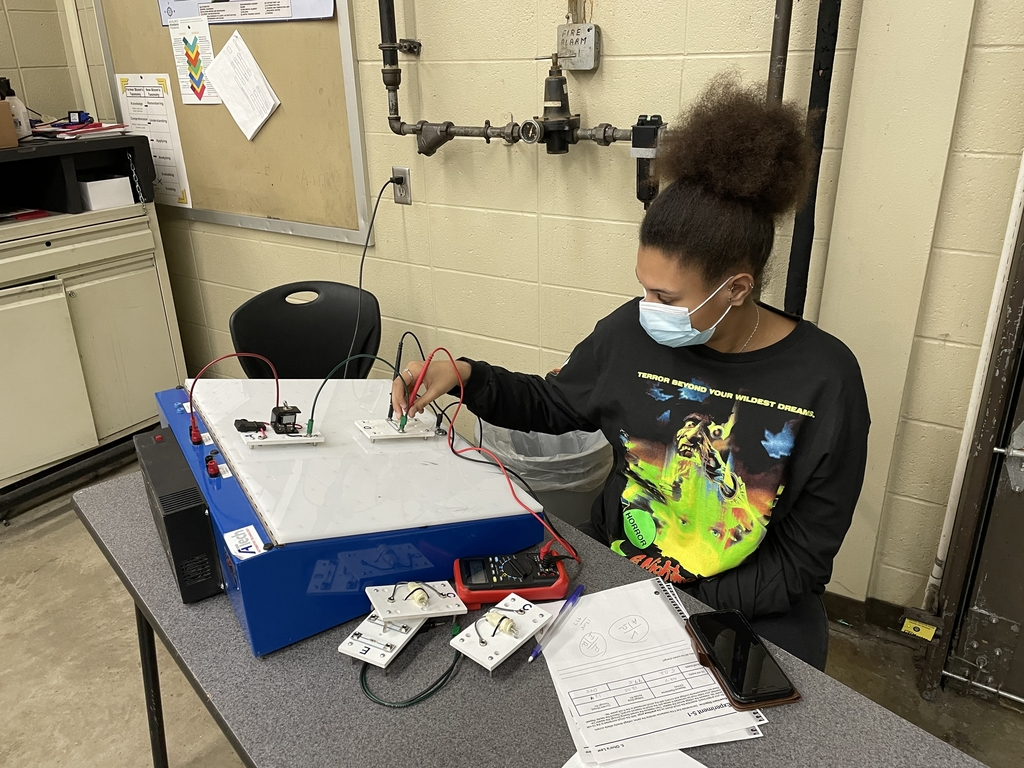 Student in Auto Service learning on electrical training board.