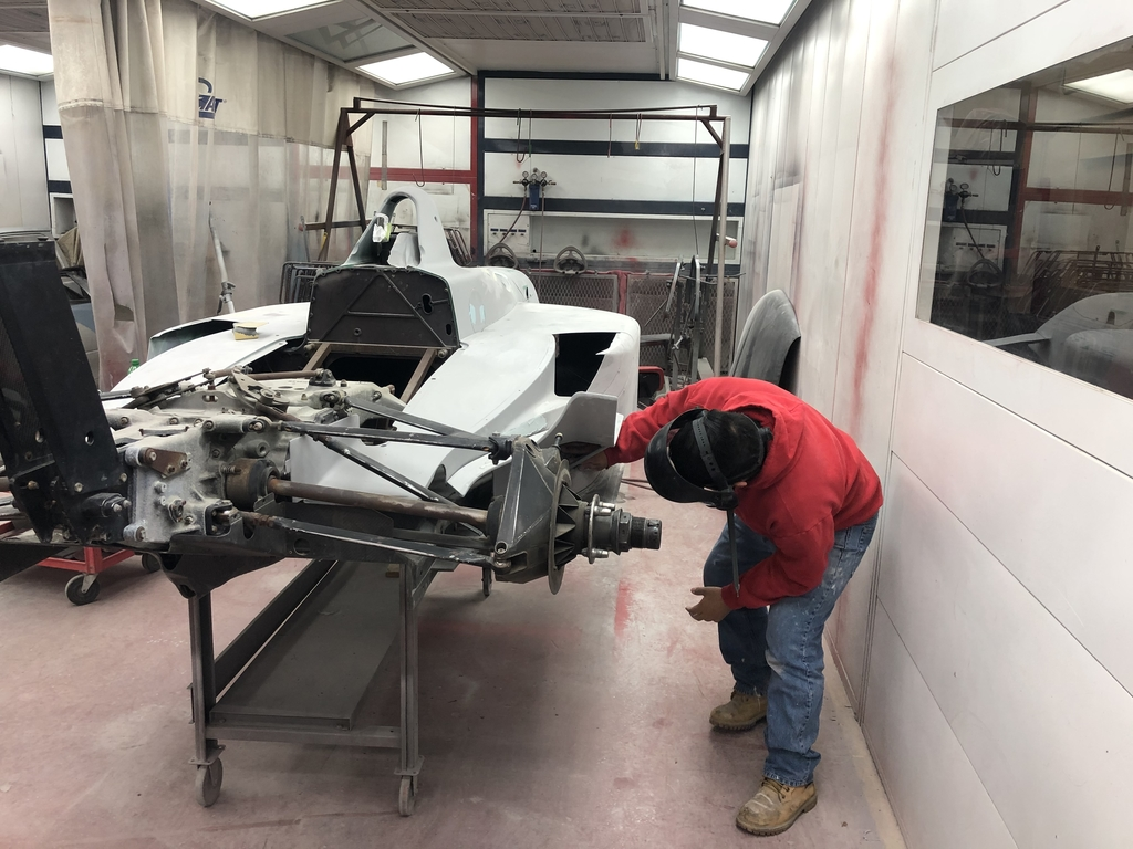 Student prepping Indy Car to paint.