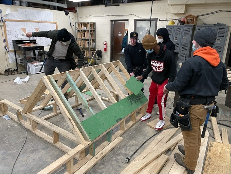 Students learning how to build a roof in Construction Trades.