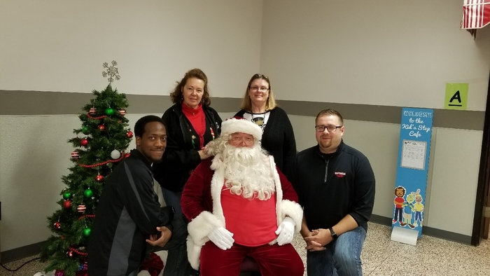 Hawthorne front office staff sitting around Santa.