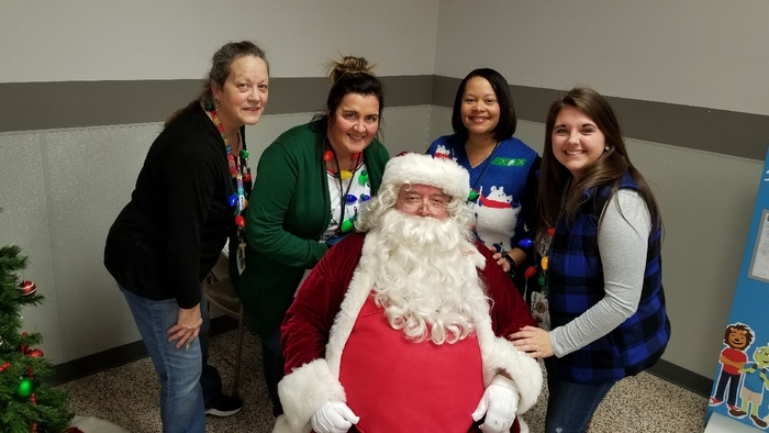 Third grade team sitting around Santa.