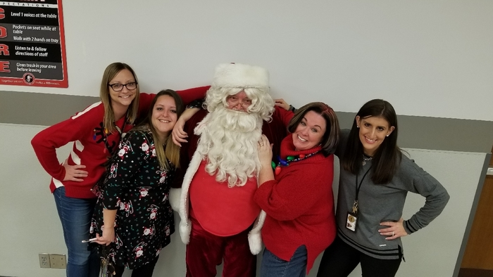 Kindergarten team sitting around Santa.