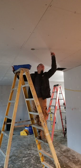 Student standing on a ladder while finishing drywall on the ceiling of the Construction Trades home.