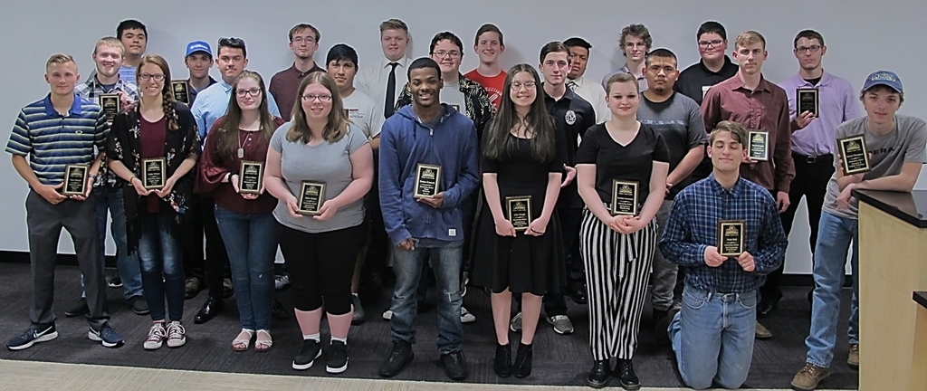 Students in the ETE department showing their Outstanding Student Award plaques.