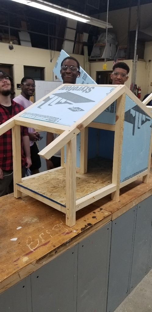 Students in our Intro to Construction class working on building dog houses.