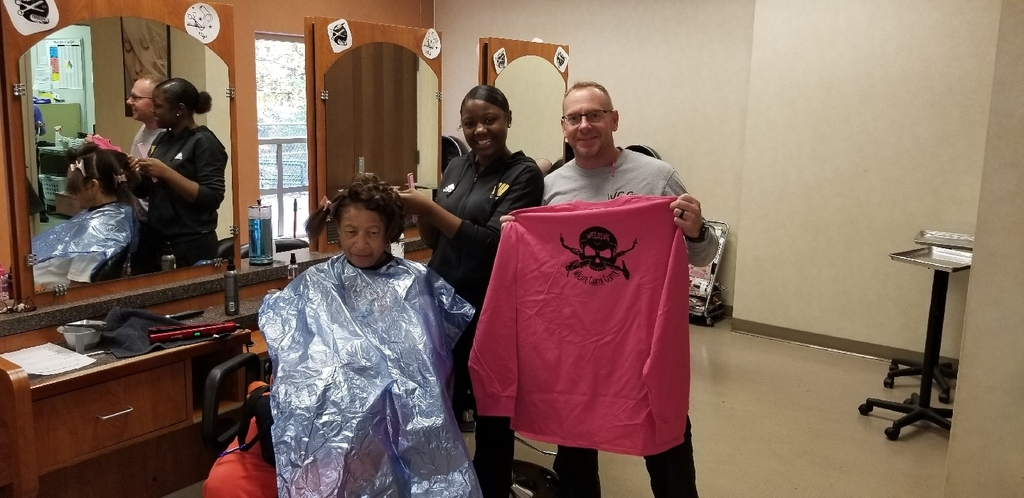 Mr. Ferguson awards a Welding T- Shirt to a cosmetology girl who won his Welding competition.