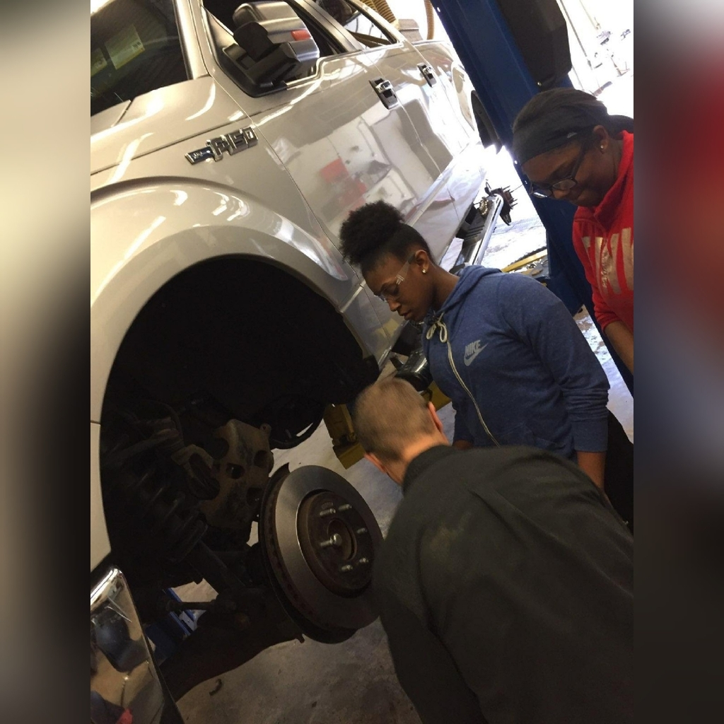 Instructor showing students how to change a tire